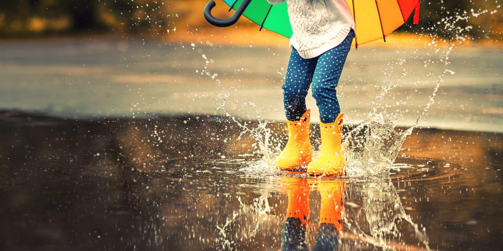 Enfant avec un parapluie qui saut dans une flaque d'eau